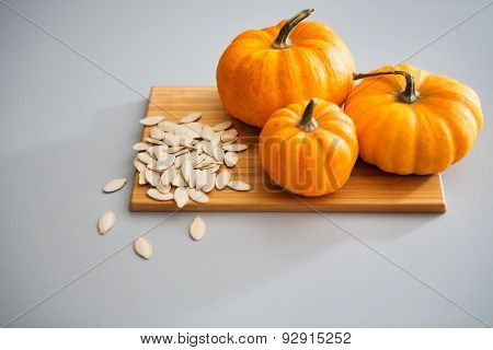Closeup Of Miniature Pumpkins And Seeds On A Cutting Board