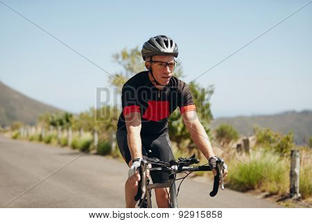 Young Man Riding Bicycle On Open Road