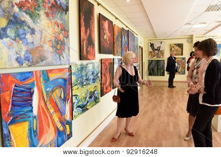 ST. PETERSBURG, RUSSIA - JUNE 7, 2015: Head of exhibition department Svetlana Yanchenko talks with spectators at the first exhibition of the project