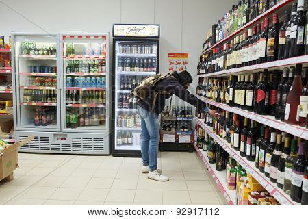 MOSCOW, RUSSIA  -  APRIL 07, 2015: Woman choosing a bottle of wine in supermarket store Pyaterochka. Supermarket Pyaterochka with the most affordable prices. Russia's largest retailer.