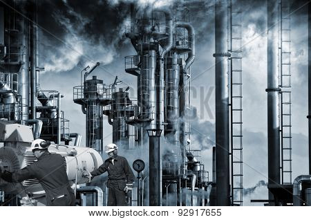 two workers with pipelines machinery, smoke, smog and industrial refinery in background