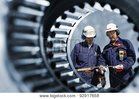 engineers, workers seen through a giant cogwheel and gear axle