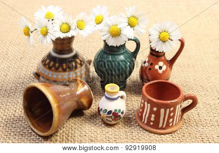 Decorative Ceramic Vases And White Daisies On Jute Canvas