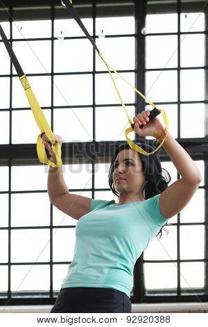 TRX. Beautiful woman at gym