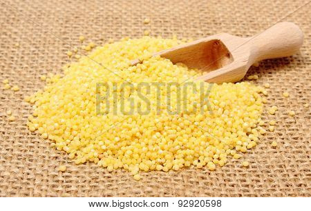 Heap Of Millet Groats With Wooden Spoon On Jute Canvas