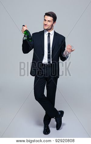 Full length portrait of a smiling businessman holding bottle with champagne and glass over gray background