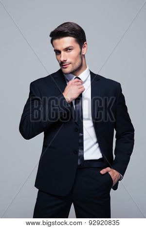 Handsome businessman straightening his tie over gray background and looking at camera