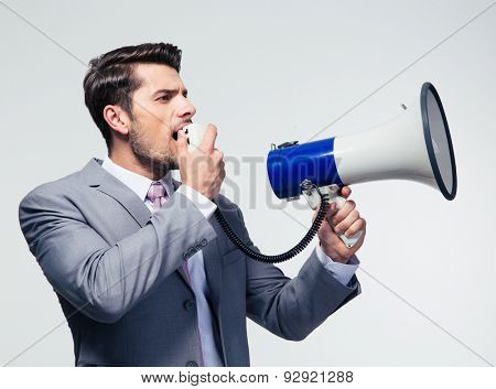 Businessman shouting in megaphone over gray background. Looking away