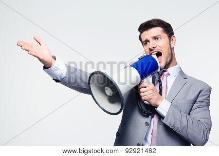 Handsome businessman screaming in loudspeaker over gray background