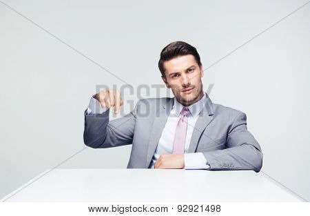 Confident businessman sitting at the table pointing finger down over gray background. Loooking at camera