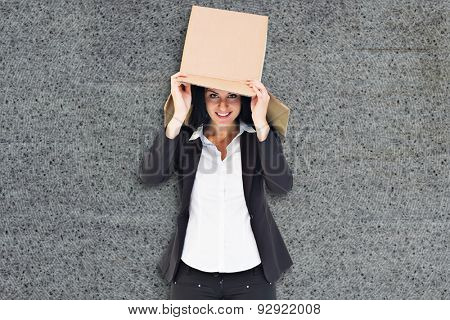 Businesswoman lifting box off head against grey background