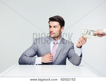 Businessman sitting at the table and taking bribe over gray background. Looking away