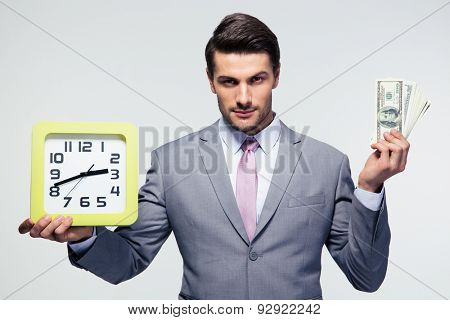Handsome businessman holding money and clock over gray background. Looking at camera