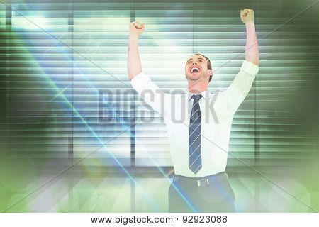 Handsome businessman cheering with arms up against window overlooking city