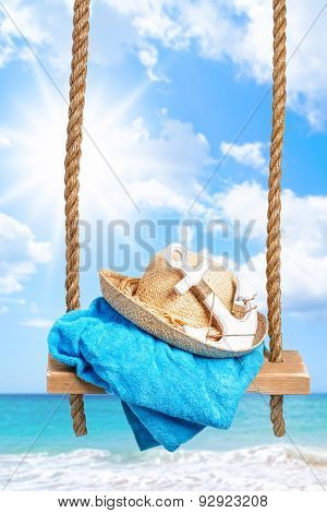 Summer swing with beach towel and anchor against an ocean blur background