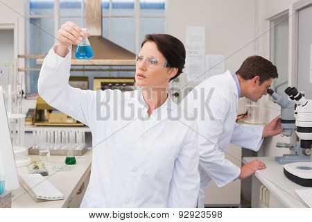 Scientists working with microscope and beaker in laboratory