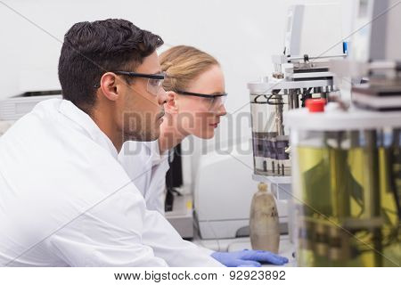 Concentrated scientists observing together in laboratory