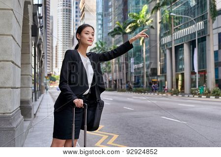 traveling asian chinese business woman calling for taxi cab from city street sidewalk