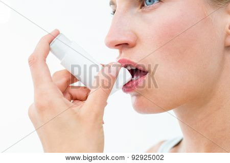 Blonde woman taking her inhaler on white background