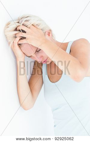 Sad blonde woman with head pain holding her head on white background