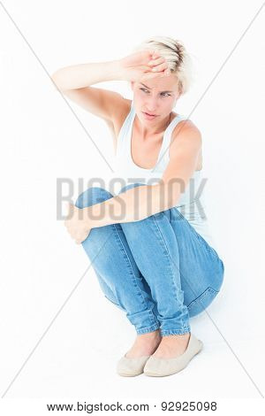 Crouching sad woman holding her hand on white background