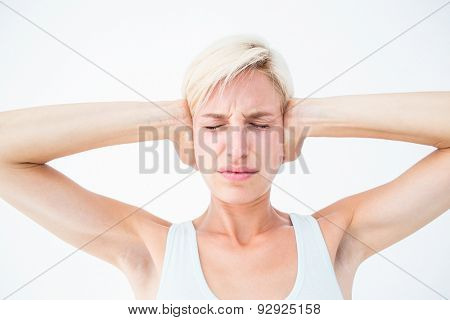 Upset woman covering her ears on white background