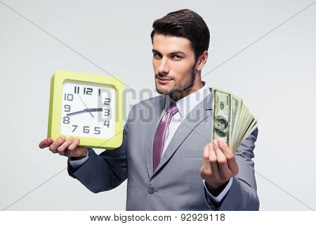 Confident businessman holding money and clock over gray background and looking at camera