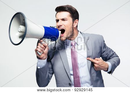 Confident businessman shouting in loudspeaker over gray background