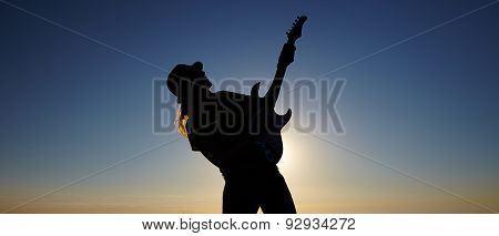 Silhouette of female busker in front of sunrise