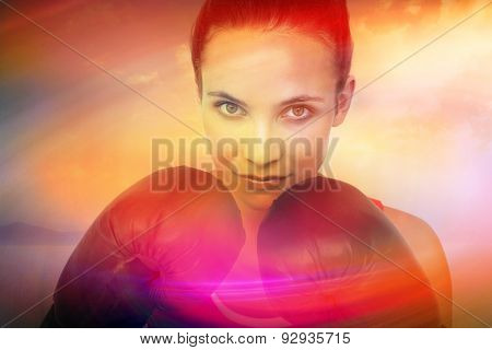 Close-up portrait of a determined female boxer against desert landscape