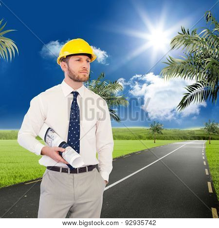 Young architect posing with hard hat and plan against road leading out to the horizon