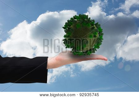 Businesswomans hand presenting against cloudy sky