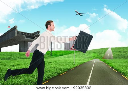 Businessman walking with his briefcase against road leading out to the horizon