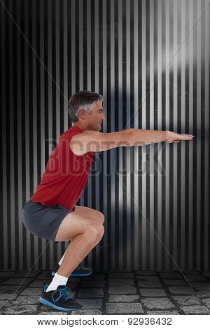 Fit man doing a squat against dark grey room