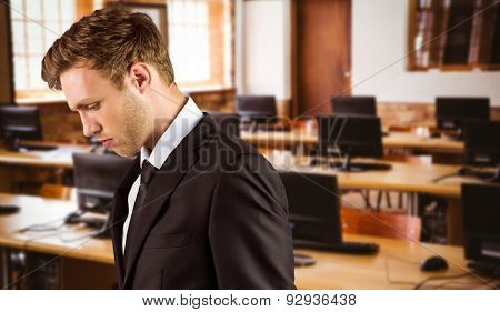 Young handsome businessman looking down against computer room
