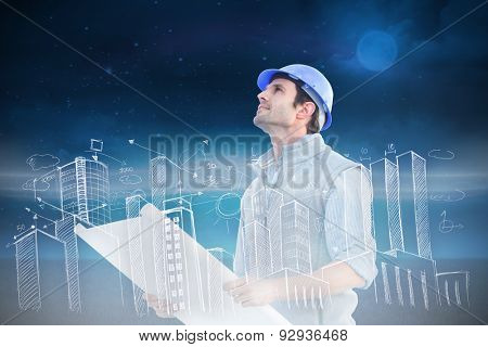 Architect with blueprint against green field at night