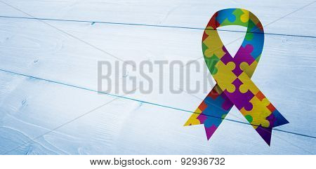Autism awareness ribbon against bleached wooden planks background