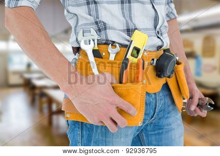 Cropped image of technician with tool belt around waist against workshop