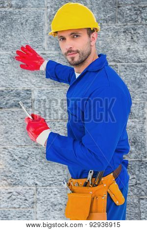 Handyman holding spanner against grey