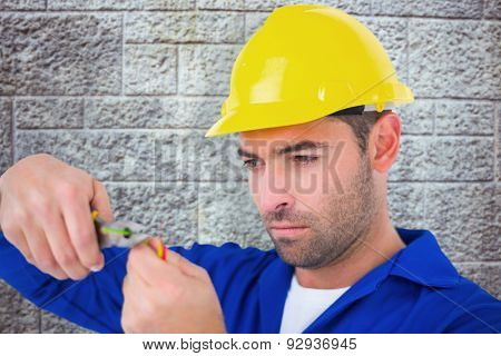 Electrician wearing hard hat while cutting wire against grey brick wall