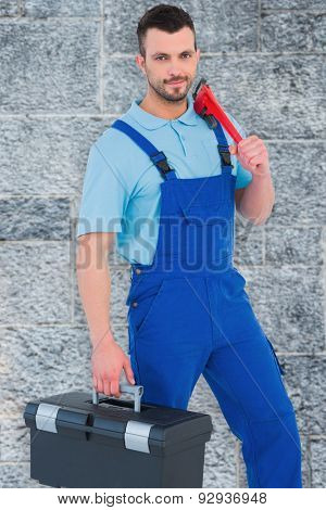 Repairman with toolbox and monkey wrench against grey