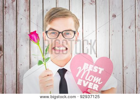 Geeky hipster holding a red rose and heart card against wooden planks