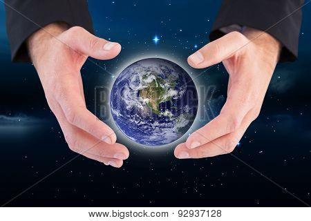 Businessman holding hand out in presentation against stars twinkling in night sky