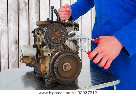 Male mechanic repairing car engine against digitally generated grey wooden planks