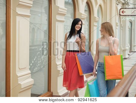 Beautiful Chatting Young Women Are Walking Through The Fancy Shop With The Colourful Shopping Bags.