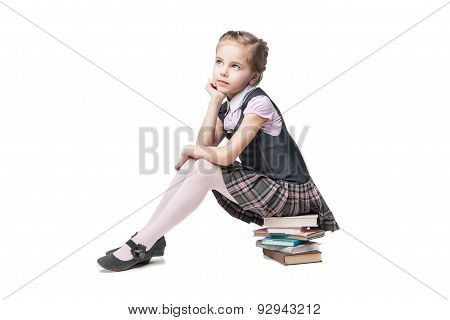Beautiful little girl in school uniform with books sitting on the floor
