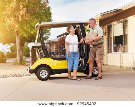 active senior couple coming home with groceries on golf cart