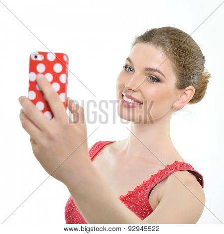 Young smiling woman making self photo. Studio shot of attractive girl with smart phone getting selfie over white background.