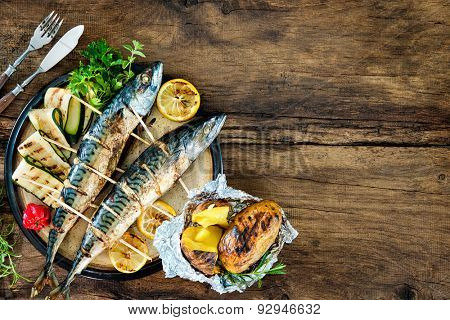 Grilled mackerel fish with baked potatoes on wooden table