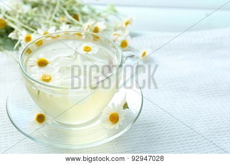 Glass of cold chamomile tea with ice cubes and chamomile flowers on color wooden background